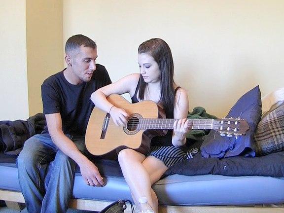 Učitel na kytaru si užívá se žákyní